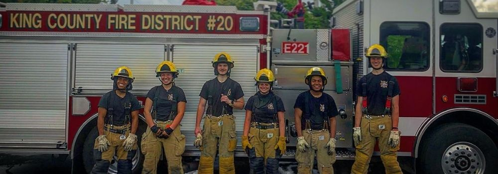 Firefighters standing in front of a fire truck.